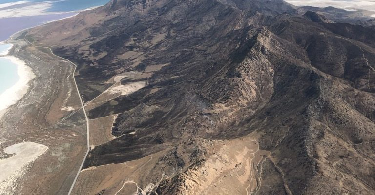Aerial view looking down at a ridgeline with a burn scar and smoke coming of the far end of the ridge.