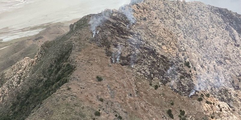 View from a helicopter looking down on a mountainside burning in the Tabby Canyon Fire