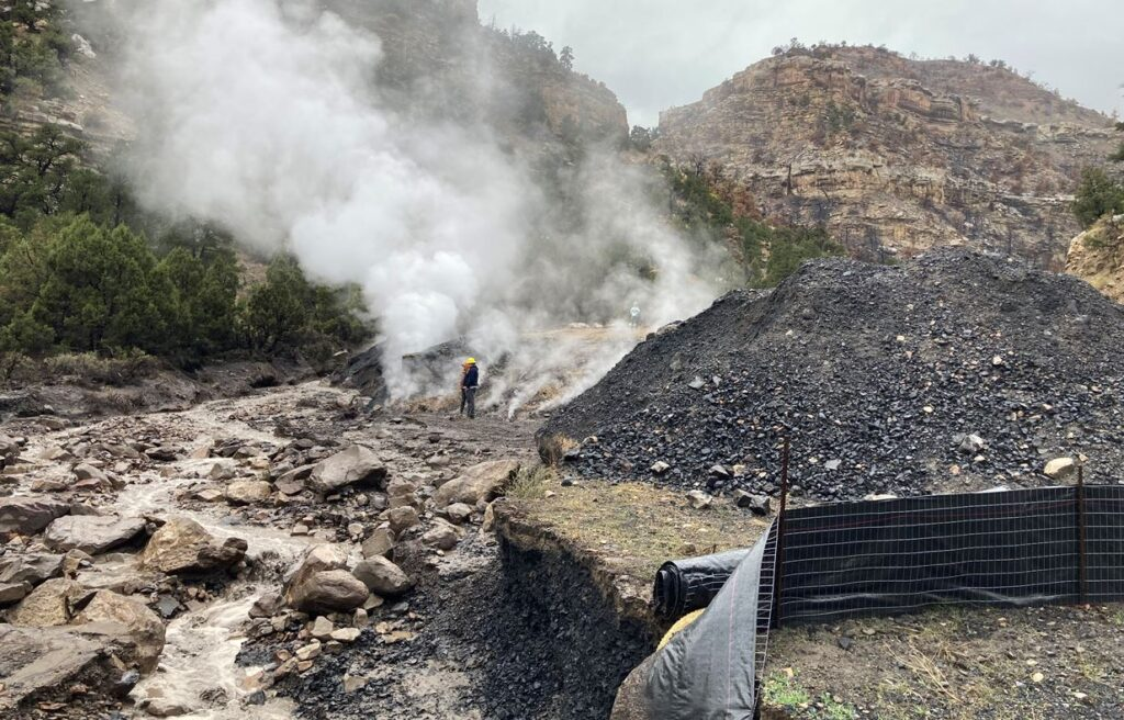 Coal hot spot with firefighter standing nearby. Mountains in the background.